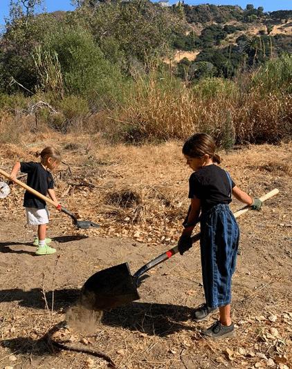 Reign and Penelope shovelling dirt before planting trees at Topanga State Park in California (Photo: @kourtneykardashian/Instagram)