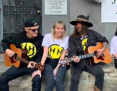 Cody Simpson, Miley Cyrus and Billy Ray Cyrus hang out with homeless youth at My Friend's Place. (Photo via @happyhippiefoundation/facebook)
