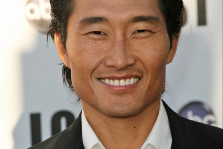 Daniel Dae Kim smiles at a red carpet event. He is a handsome Korean-American actor with black hair, wearing a black jacket and a white shirt underneath with the top button undone.