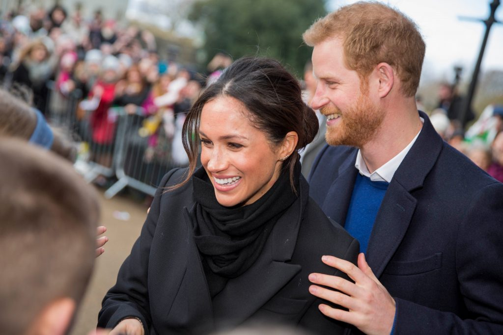 Duke and Duchess of Sussex shake hands with fans at a public event. She wears a dark coat and his her hair tied back. He wears a white shirt and blue sweater under a dark coat. He stands behind her with one hand on her arm. They are both laughing.