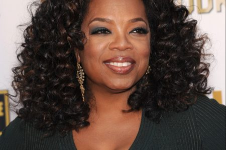 Oprah smiles at a red carpet event. she has curly black hair that sits on her shoulders and wears a V-neck dress that is a forest green in colour.