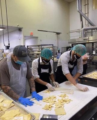 Harry and Meghan preparing food in the kitchens at Homeboy Industries (Photo: @HomeboyIndustries/Instagram)