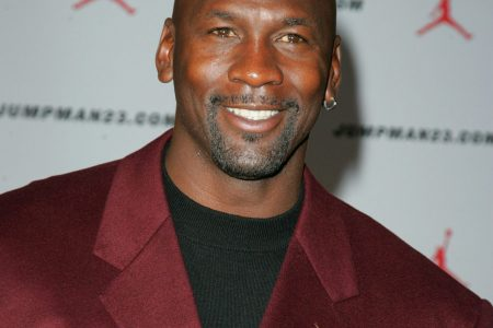 Michael Jordan smiles at a red carpet event. He wears a burgundy suit with a black t-shirt.