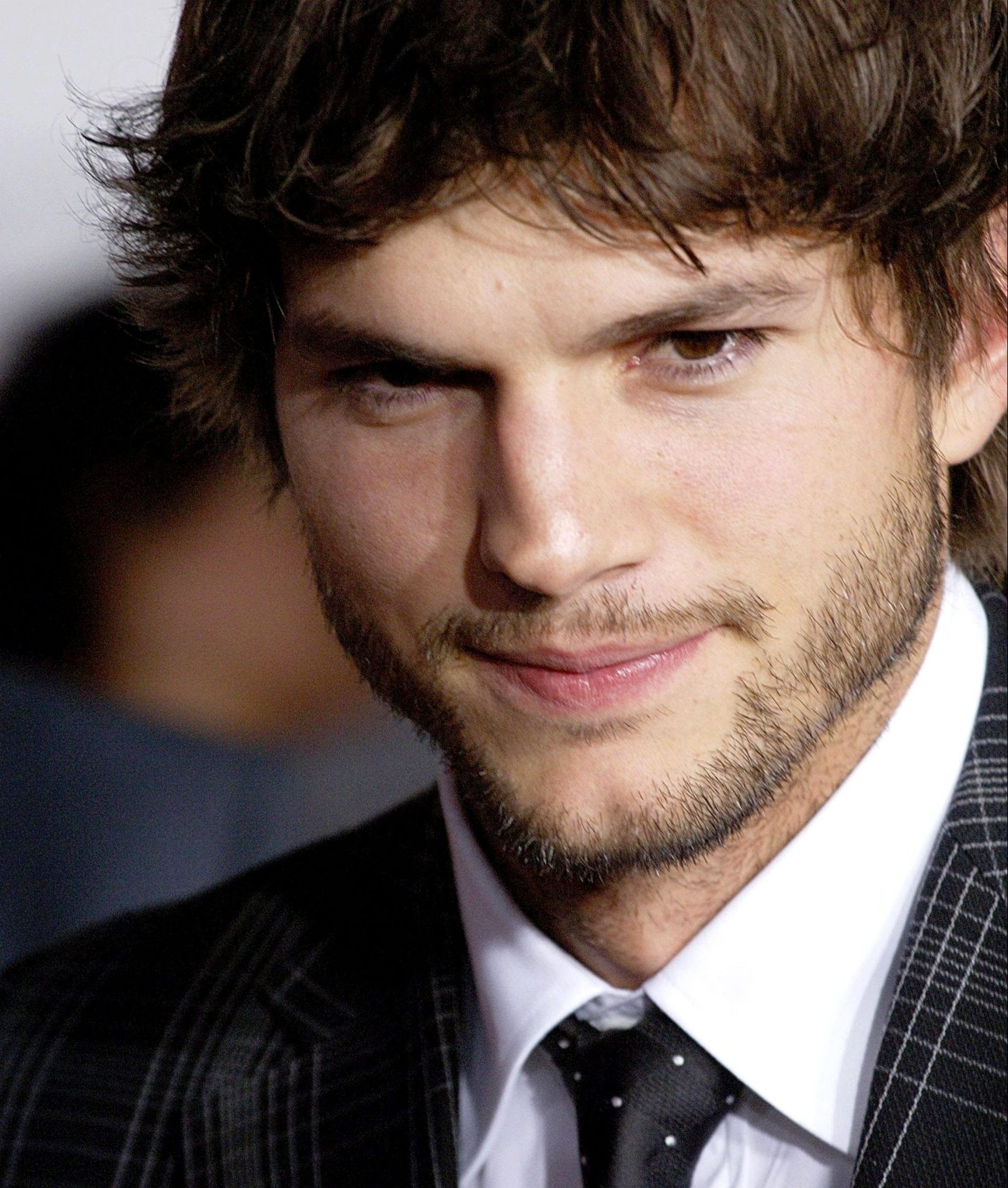 A close up of Ashton Kutcher's face. He has stubble on his upper lip, chin and jawline andwears a white shirt, black tie and dark suit jacket.