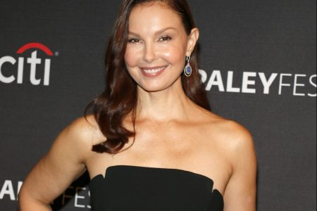 Ashley Judd smiles at a red carpet event wearing a strapless black dress.