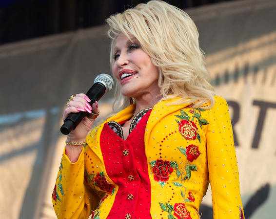 Singer Dolly Parton standing on stage with a microphone, smiling. She wears a yellow jacket with red flowers on them.