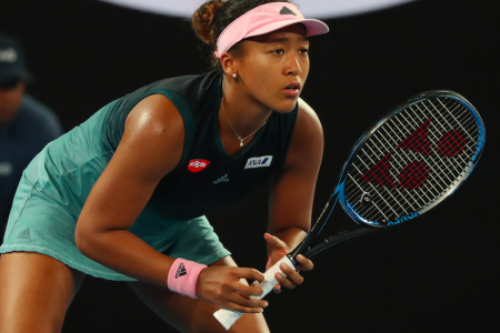 Naomi Osaka ready to play at a tennis event. She wears a pink visor and a blue and green tennis dress. She holds a racquet in her hands and is leaning forward.