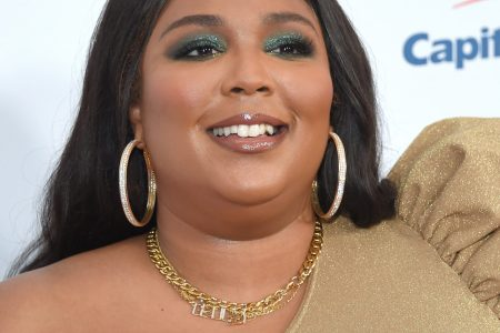 Lizzo smiles at a red carpet event. Her long black hair sits straight, behind her shoulders. She wears big gold hoop earrings and a one shoulder coffee-coloured dress.