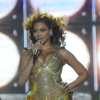 Beyoncé dancing on stage in a gold leotard that accentuates her hips. She has her right hand on her hip while her other hand holds a microphone to her mouth. Her hair is blowing away from her face and there are giant circular lights in the background.