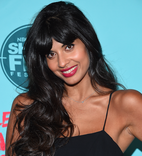 Jameela Jamil smiles at a red carpet event. She has long black hair and wears a black dress with thin straps.