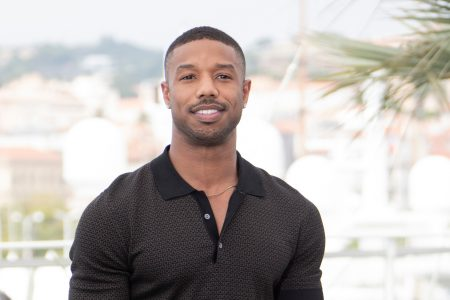 Actor Michael B. Jordan smiles while wearing a black shirt with the top buttons undone.