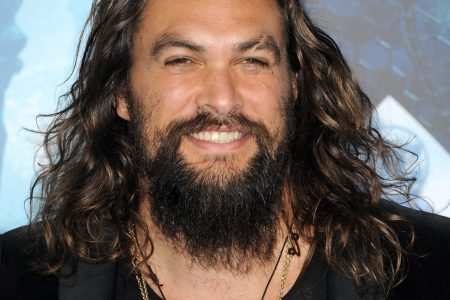 Jason Momoa smiling at the camera with brown shoulder-length, wavy hair, a moustache and short beard. He's wearing a black suit and has a cream-coloured beaded necklace on.