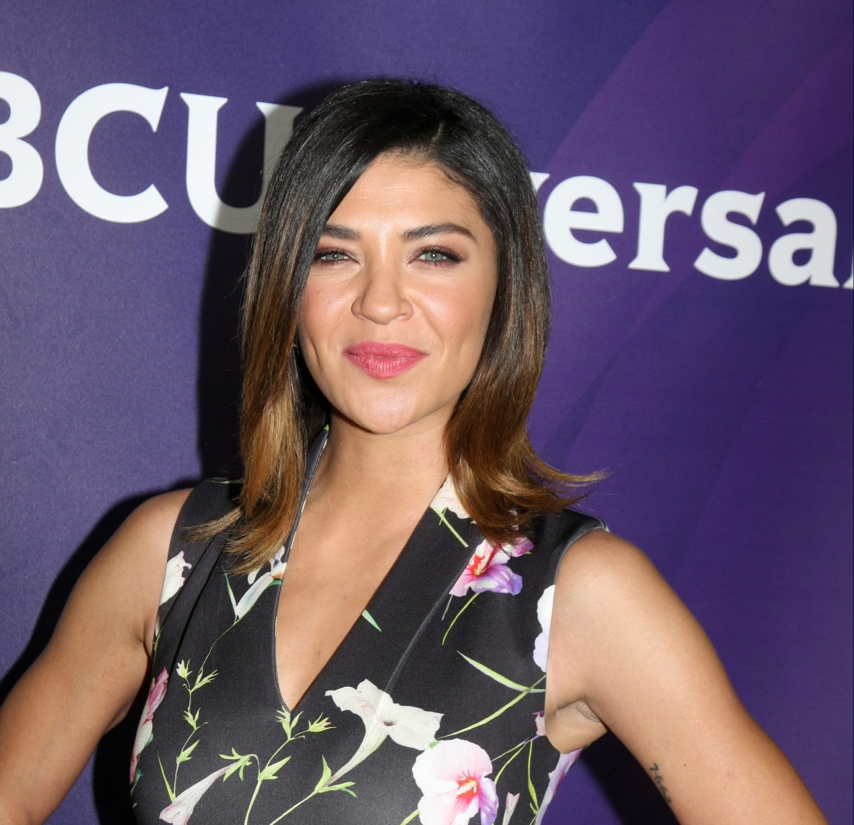Jessica Szohr smiles at a red carpet event. She has dark brown hair that sits above her shoulders. She wears a floral black sleeveless top. The background is a deep purple.