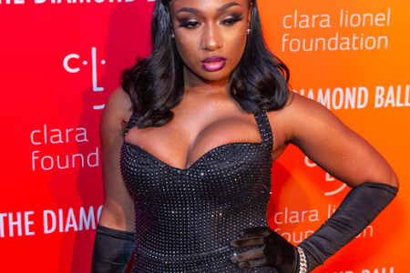 Megan Thee Stallion posing with one arm on her hip at a red carpet event. She wears a fitted, halter-neck black dress and elbow-length black gloves. Her hair is old Hollywood glam - straight with curls at the bottom.