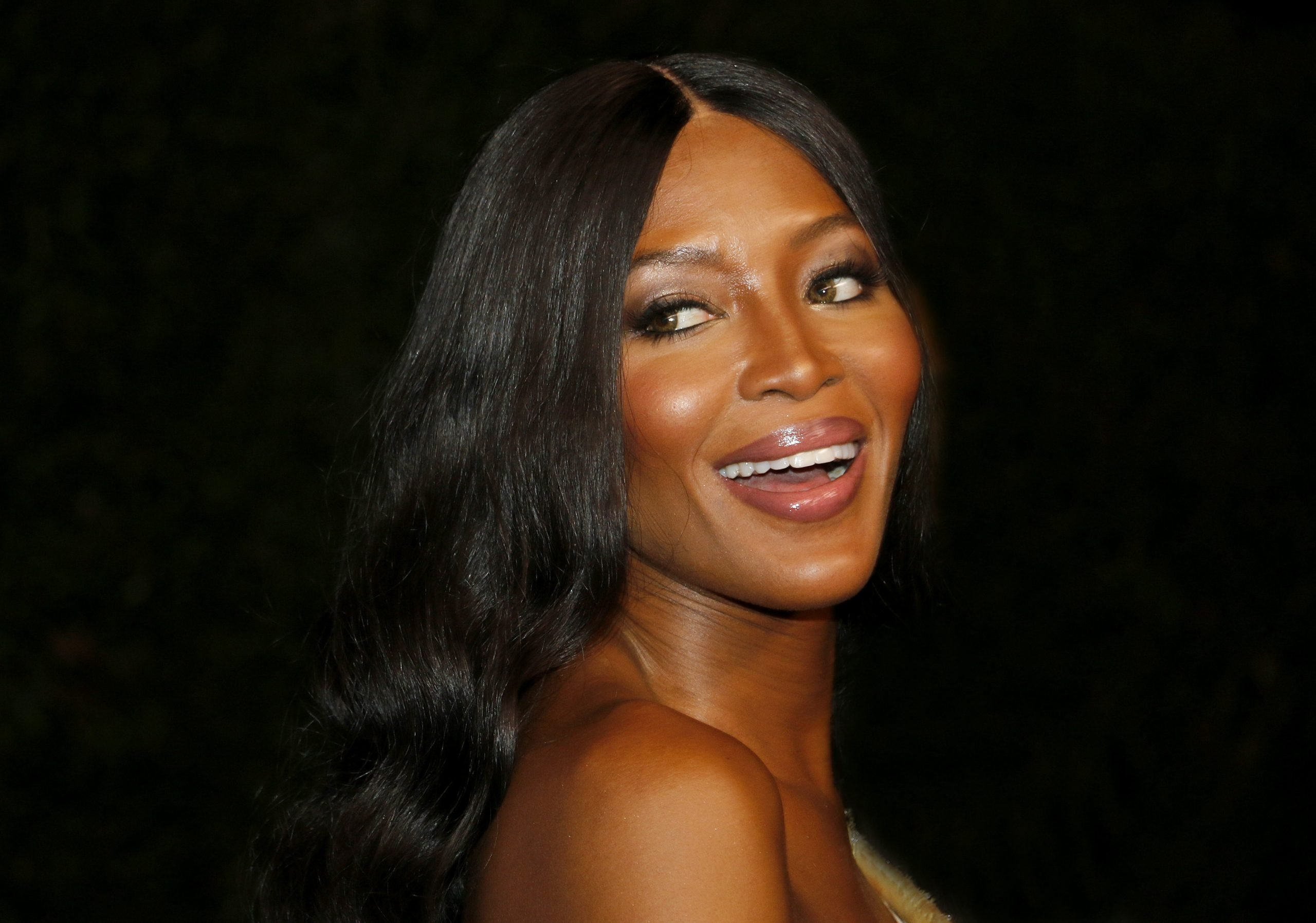 Naomi Campbell smiles at a red carpet event. She has long black hair that sits behind her shoulders. Her body faces away from the camera. Her eyes look past the camera. She is glowing.