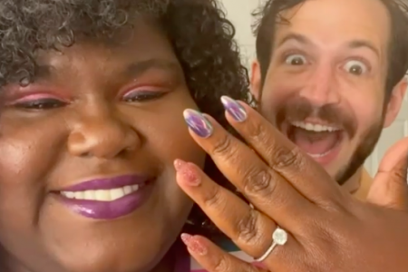 Gabourey Sidibe holds up her hand with a sparkly engagement ring on her finger. Brandon Frankel stands behind her with a huge smile on his face!