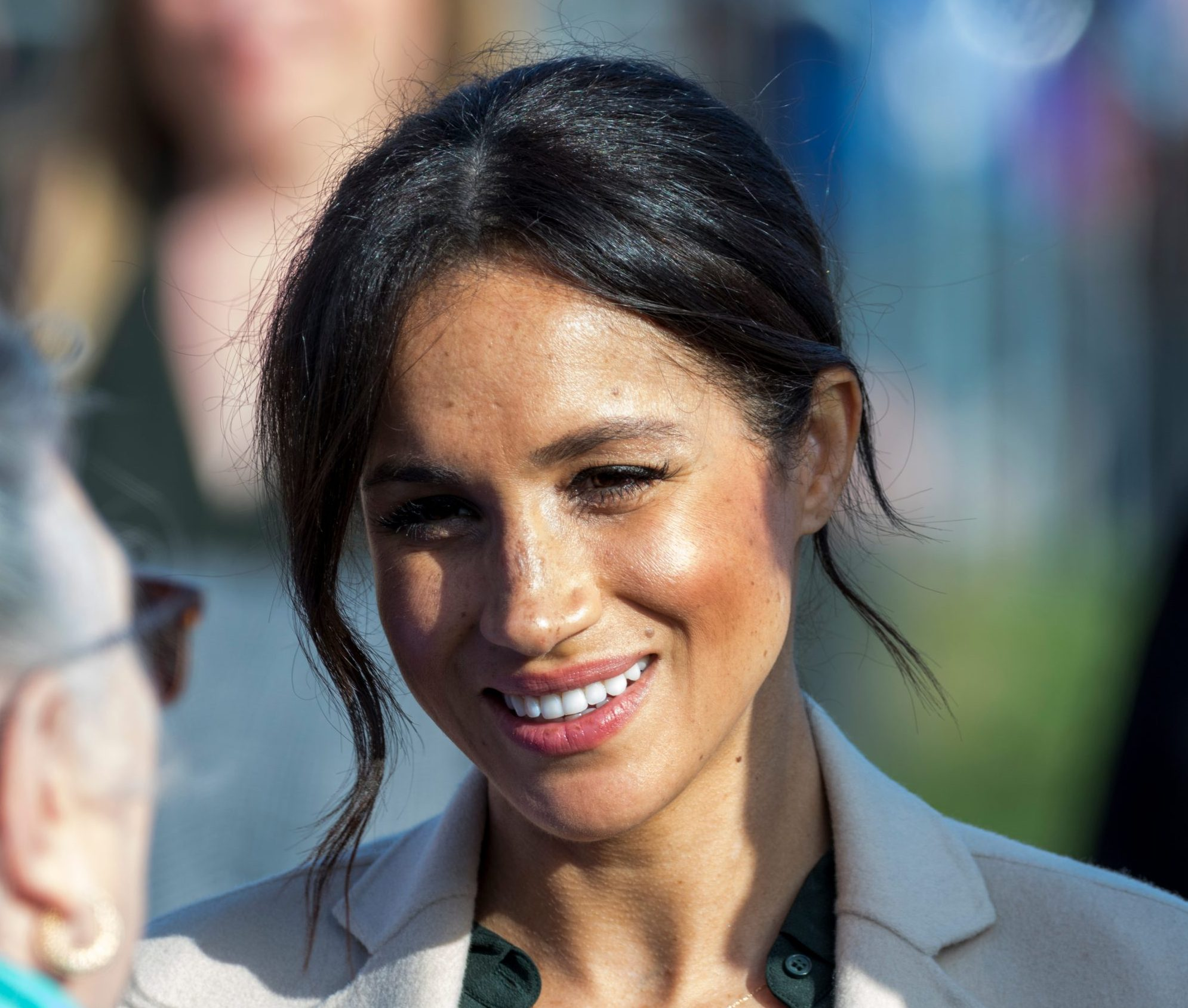 A close-up photo of Meghan Markle from the neck up. Her black hair is tied back though a few strands dangle around her face. The sun is shining on her and she gives a small smile as she speaks with an elderly lady.