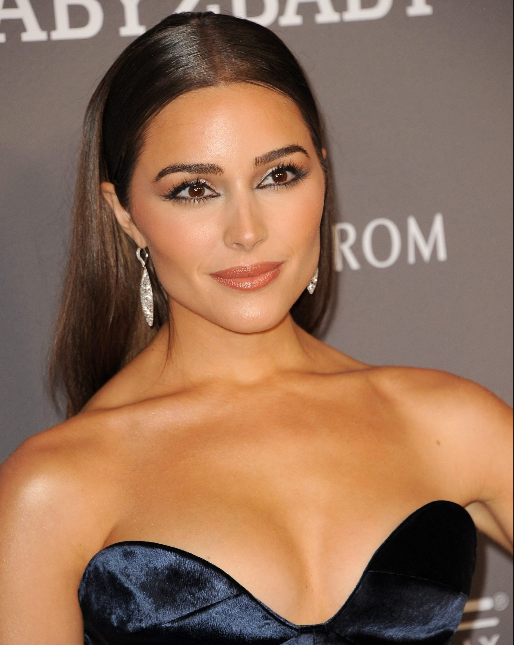 Actress Olivia Culpo wears a strapless navy dress, has her long brown hair out, behind her shoulders and sparkling earrings that dangle next to her neck. She is smiling at a red carpet event.