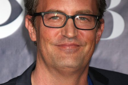 Actor Matthew Perry smiling at a red carpet event. He wears black-framed glasses, a dark suit jacket and an electric blue t-shirt.