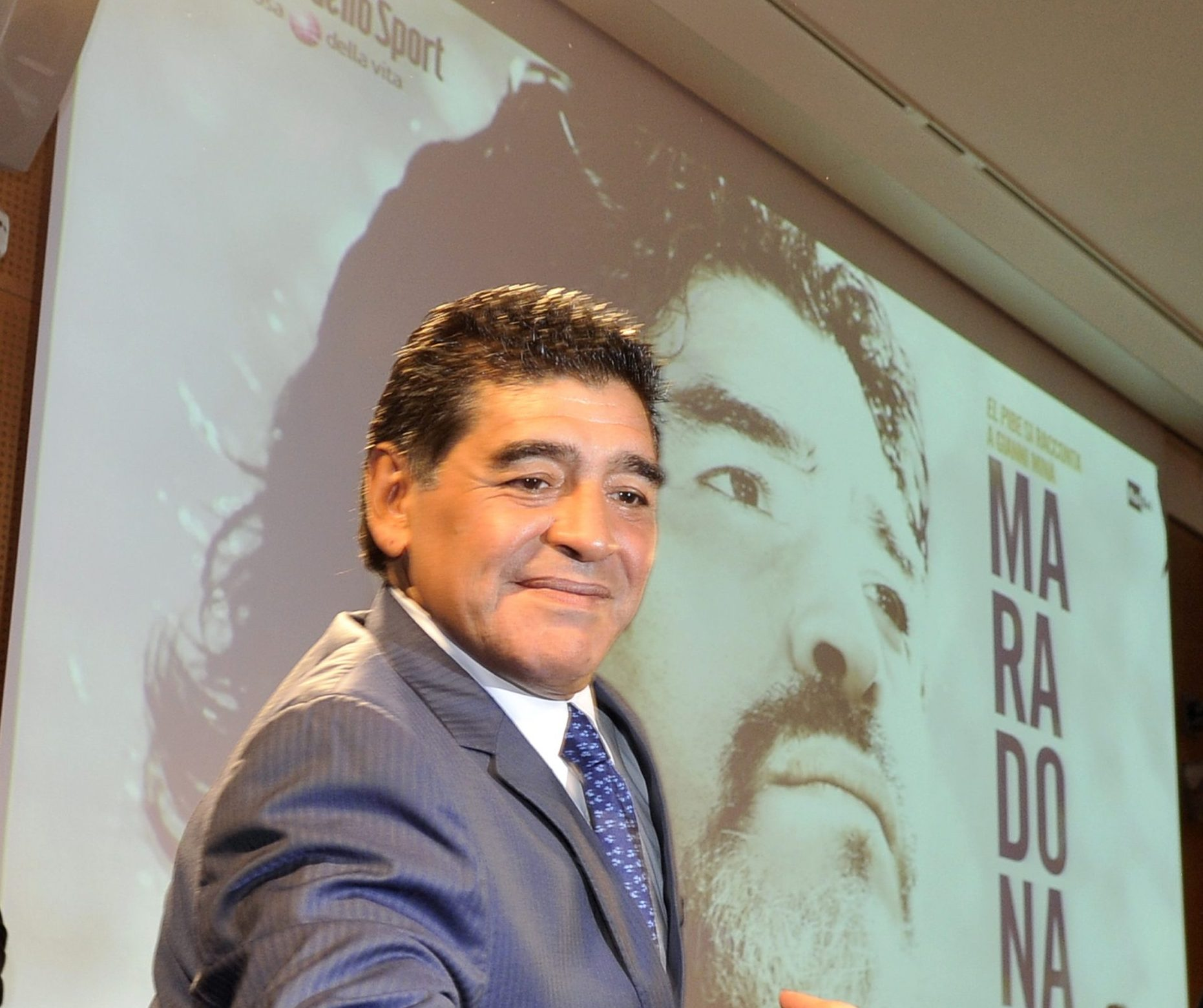 """Diego Maradona wearing a grey suit, white shirt and blue tie. He smiles. Behind him is a screen showing the """"Maradona"""" movie."""