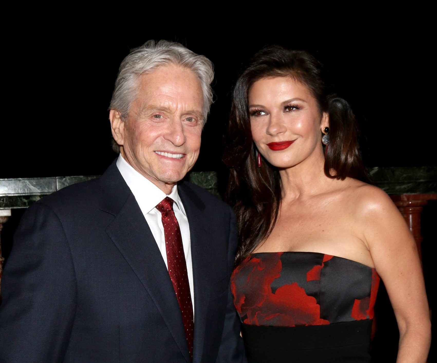 Michael Douglas dressed in a black suit, white shirt and red tie, smiles while standing next to Catherine Zeta-Jones who is wearing a red and black strapless dress, has her long dark hair out and red lipstick on.