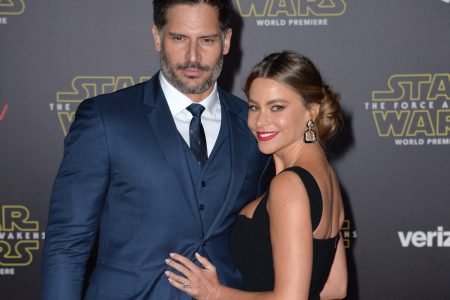 Joe Manganiello and Sofia Vergara smiling at a red carpet event. He has short, dark hair, a moustache and a greying beard. He wears a dark blue suit, white shirt and a black tie. Sofia has her brown hair tied back at the nape of her neck. She wears a fitted black, sleeveless dress and red lipstick. Her body faces his and she looks over her shoulder at the camera.