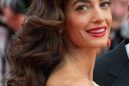 Amal Clooney smiling at a red carpet event. She has long wavy brown hair and is wearing red lipstick.