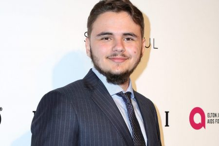 Prince Jackson smiling at a red carpet event. He wears a pinstriped, navy suit jacket, a pale blue shirt and a navy tie. He has short brown hair, some stubble and a short moustache.