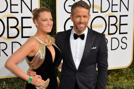 Blake Lively and Ryan Reynolds on the red carpet at the 2017 Golden Globe Awards. She wears a black and gold sleeveless dress, with her hair slicked back in a high bun. He wears a black tuxedo, white shirt and a bow tie.