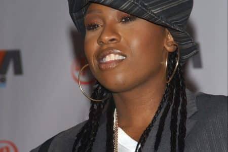 Missy Elliot wearing a striped black and grey hat, hoop earrings and her hair in braids.