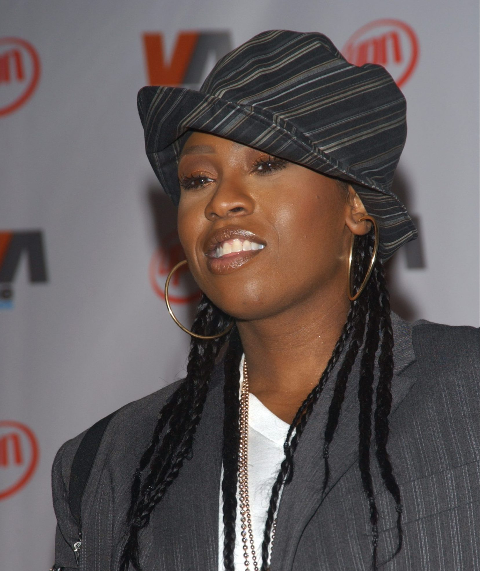Missy Elliot wearing a striped black and grey hat, hoop earrings and her hair in braids.