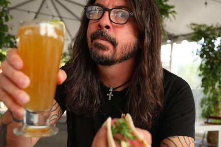 Dave Grohl holding a cocktail and the limited edition Foo Fighters taco available at Casa Vega Restaurant in Sherman Oaks, California. He has his signature long hair, glasses, a moustache and short bears. He wears a fitted black T-shirt.