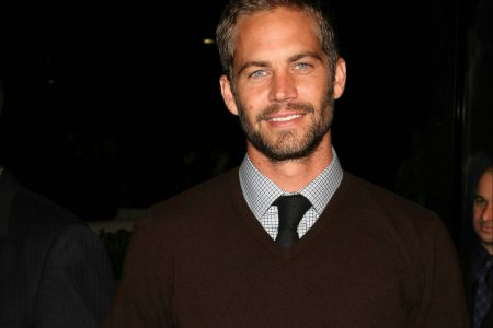 Paul Walker smiles at a red carpet event. he wears a brown jumper, with a shirt and tie underneath.
