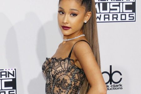 Ariana Grande poses for a photo at a red carpet event. She has her hair in a high ponytail, wears a deep red lipstick and has one hand on her hip.