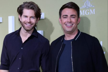Jaymes Vaughan and Jonathan Bennett at a red carpet event. Jaymes wears a blue shirt and has some facial stubble. Jonathan wears a blye t-shirt with a black jacket on top. They are both smiling.