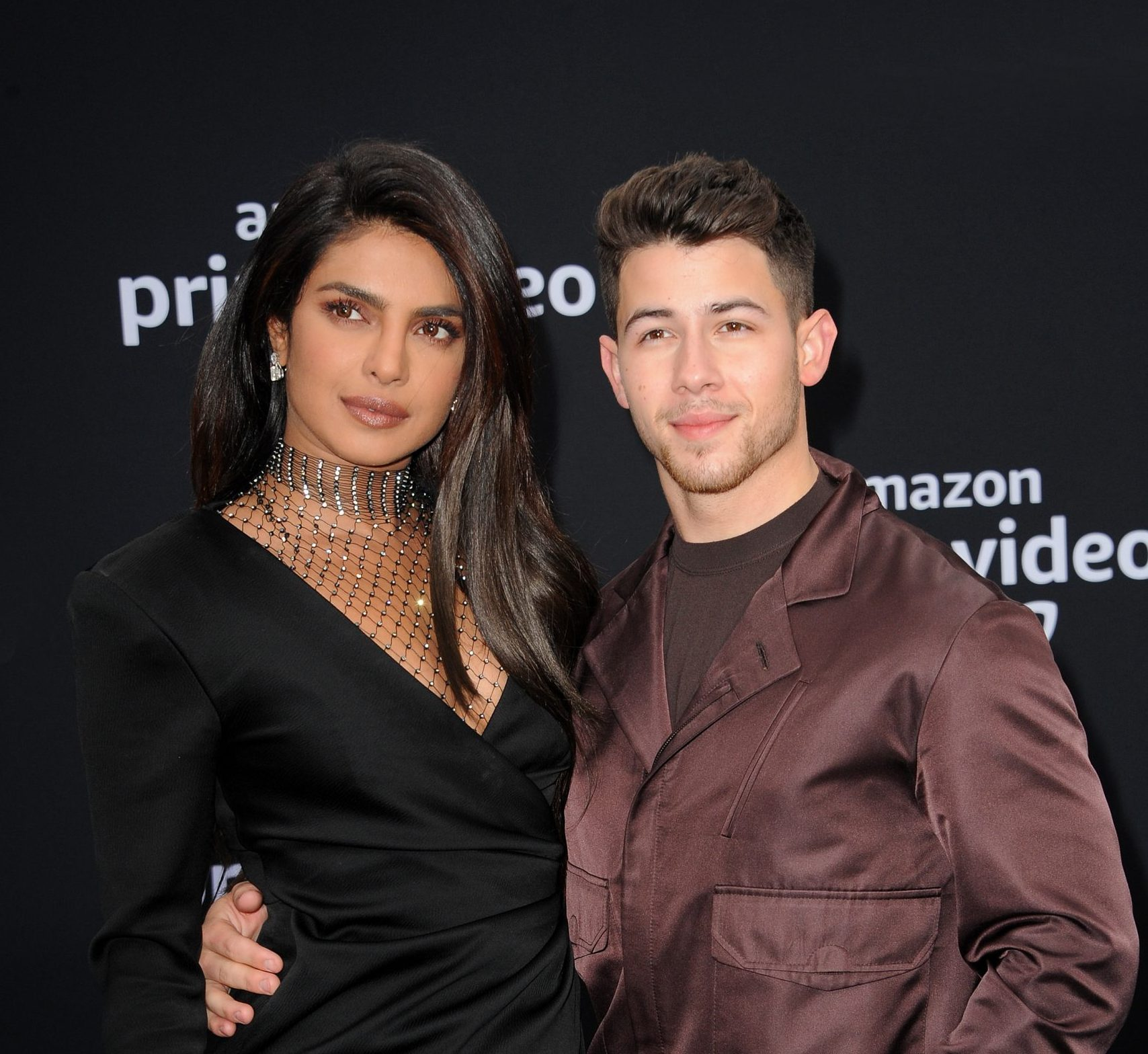 Priyanka Chopra and Nick Jonas attend a red carpet event. She wears a long sleeved black dress with her hair out and a sparkling choker around her neck. He wears a shiny brown suit with a brown t-shirt underneath. He has his arm around her waist. They are both looking past the camera and slightly smiling.