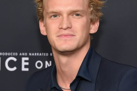 Cody Simpson smiles at a red carpet event. He has wavy, beach blonde hair and wears a black shirt with the top button undone. The background is black.