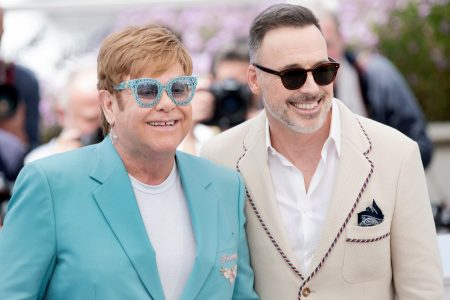Elton John and David Furnish attend a red carpet event. Elton wears an aqua-coloured jacket with matching glasses. David wears a cream coloured jacket with black sunglasses. They are both smiling.
