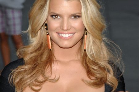 Jessica Simpson smiles at an outdoor event. She wears a black, short-sleeved dress and peach earrings. Her blonde hair sits on her shoulders in layers.