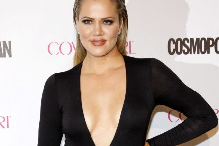 Khloé Kardashian attends a red carpet event. She wears a long-sleeved black dress with a deep V down to her waist. Her hair is slicked back behind her shoulders. She has one hand on her hip and smiles past the camera.