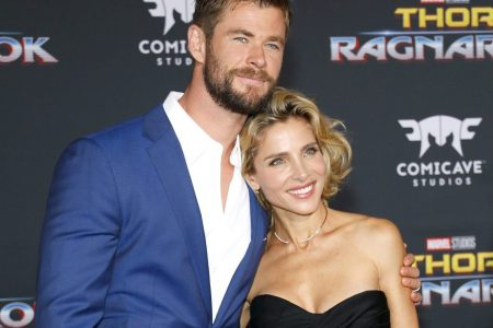 "Chris Hemsworth and Elsa Pataky attend a red carpet event. He wears a blue suit and white shirt. She wears a strapless black dress. They lean into one another and have one arm around each other. They are both smiling. The background is black and reads ""Thor Ragnarok""."