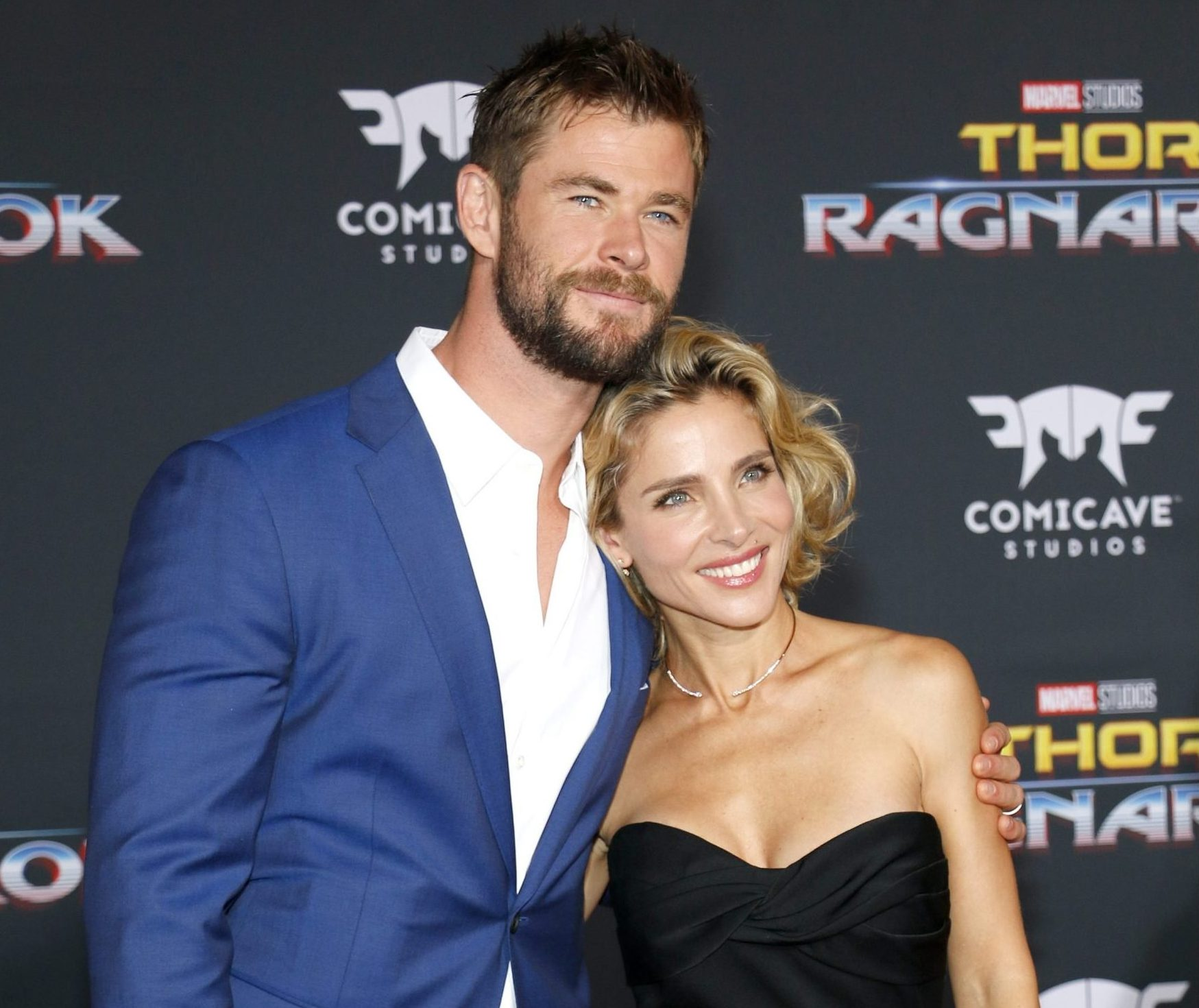 """Chris Hemsworth and Elsa Pataky attend a red carpet event. He wears a blue suit and white shirt. She wears a strapless black dress. They lean into one another and have one arm around each other. They are both smiling. The background is black and reads """"Thor Ragnarok""""."""