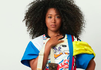 Naomi Osaka in the Louis Vuitton 2021 campaign photographed by Nicolas Ghesquière. She has an afro hairstyle, wears a bright, colourful shirt with blue sleeves and carries a brown Louis Vuitton bag.