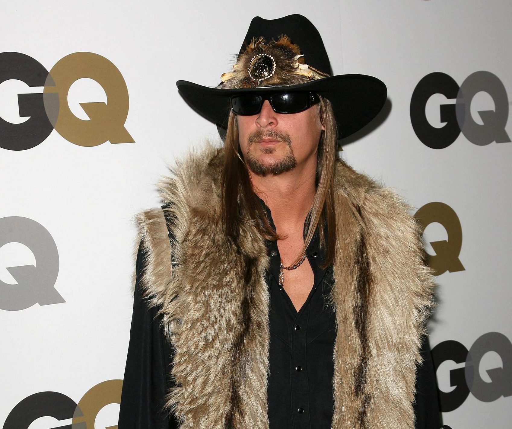 Kid Rock poses at a red carpet event. He wears a black cowboy hat, sunglasses, a fur vest and a black shirt underneath. He has long, straight hair that sits past his shoulders and a fine moustache and short beard. He looks very stylish!