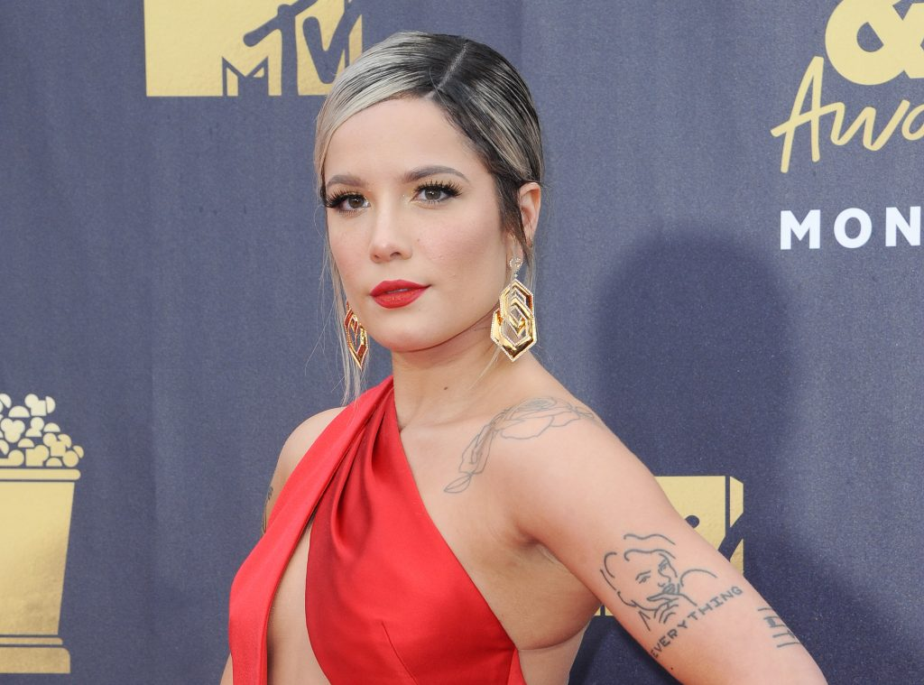 Halsey poses for photos at a red carpet event. She wears a one shoulder red dress and has matching red lipstick on. She wears gold earrings, and has tattoos down one arm.