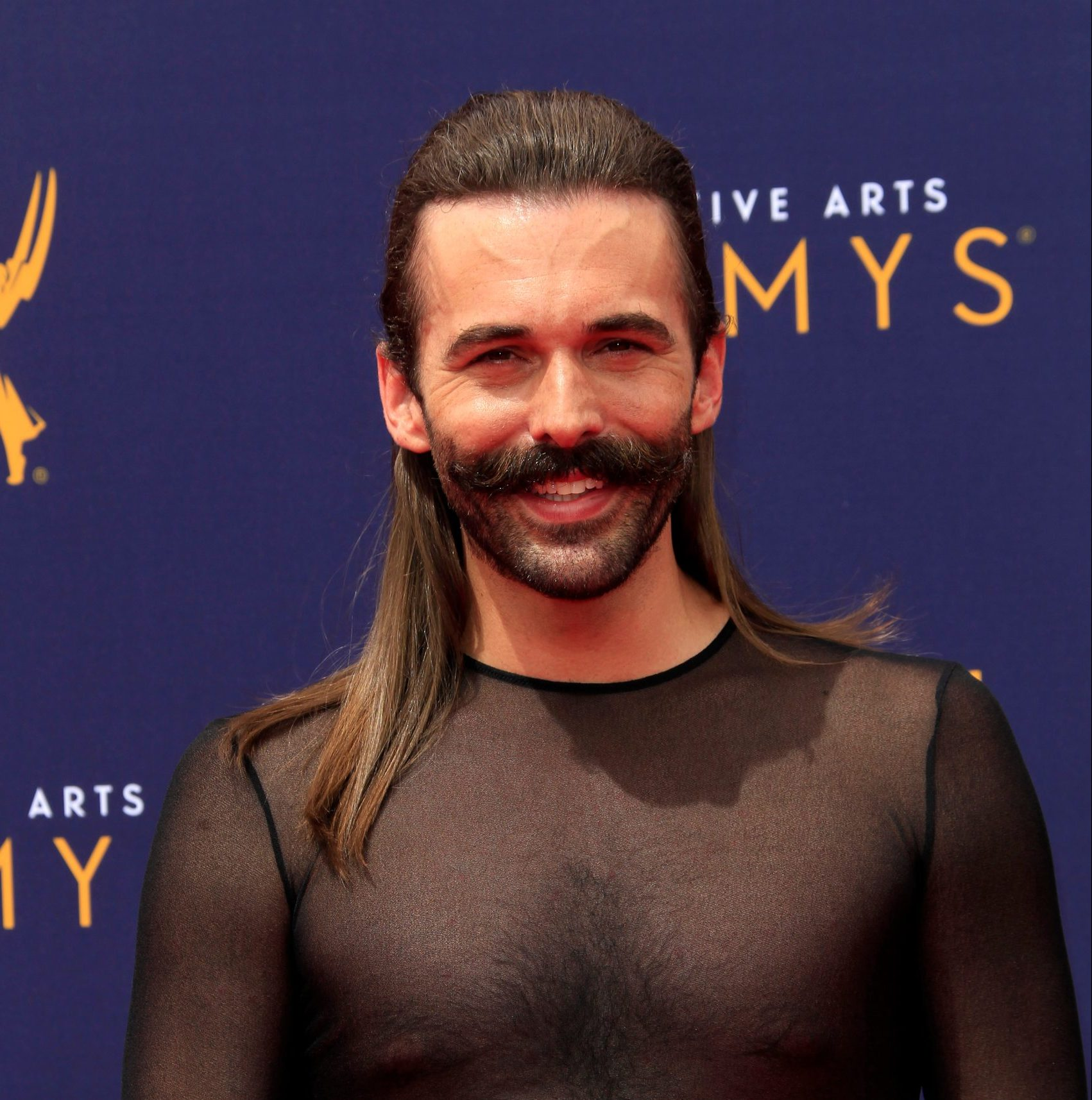 Jonathan Van Ness smiles at a red carpet event. He wears a sheer black top. His hair is half up, slicked back in a pony tail. The rest is sitting straight on his shoulders. He has a luscious, thick moustache and a short beard.