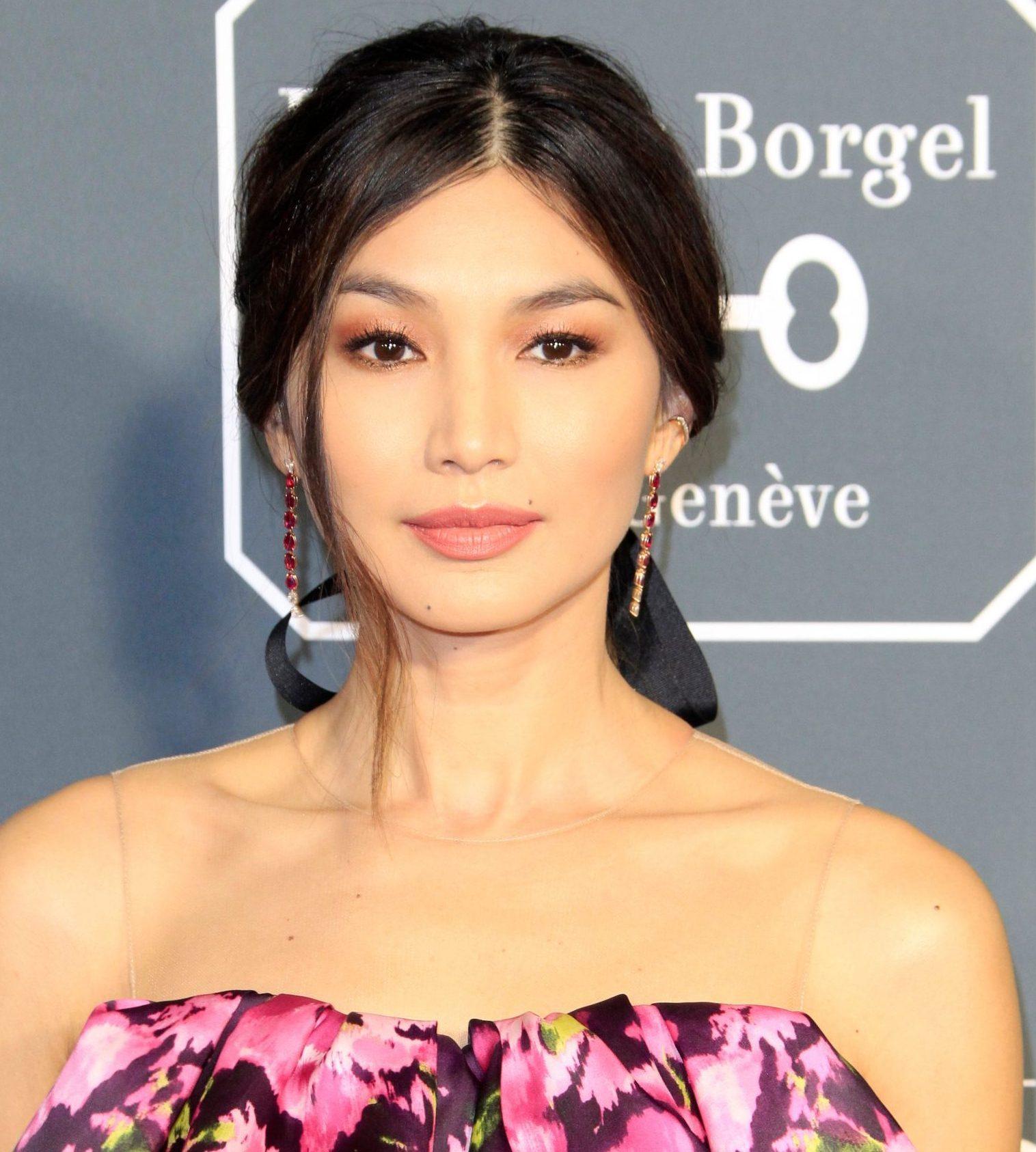 Gemma Chan smiles at a red carpet event. She wears an off the shoulder floral pink dress. Her hair is long and black, tied back in a loose ponytail.