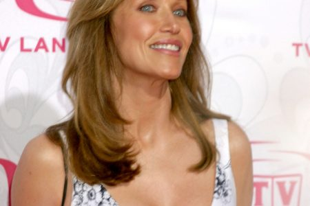 Tanya Roberts smiles at a red carpet event wearing a dazzling low cut white dress. She has brown hair that sits below her shoulders.