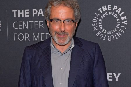Warren Leight Attends a red carpet event. He has greying hair, moustache and beard. He wears glasses and navy suit with a grey shirt underneath.
