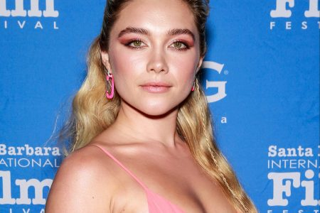 Florence Pugh attends a red carpet event. She has long blonde hair, half is tied back away from her face. She wears a pastel pink dress and has matching pink makeup.